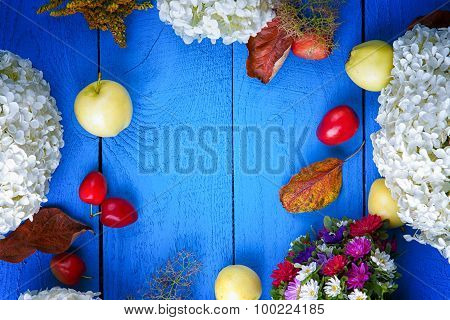Apples, flowers, leaf litters and plums on a blue wooden table