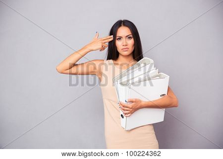 Businesswoman holding folders and making gun gesture to her head over gray background
