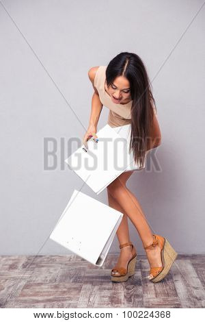 Businesswoman dropping folders on the floor over gray background
