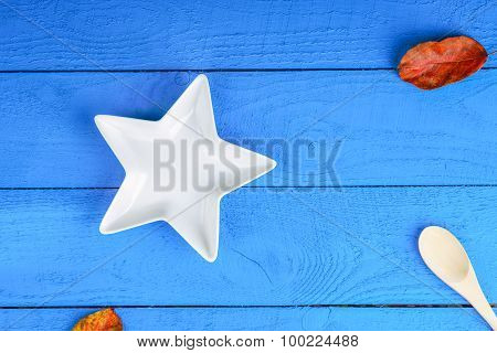 Plate, spoon and leaf litters on wooden background