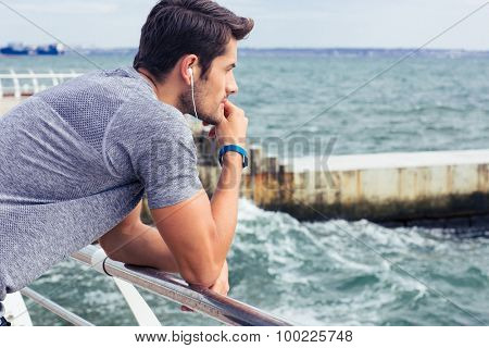 Side view portrait of a sports man looking at sea outdoors