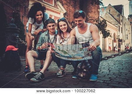Multiracial friends tourists with map in an old city