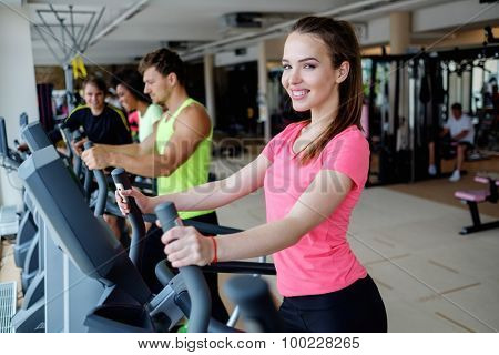 People exercising on a cardio training machines in a gym