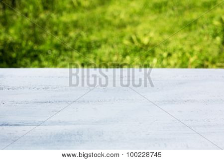 White wood deck table with foliage bokeh background Empty wooden perspective and blurred store. Ready for product display montage.