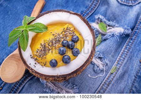 Breakfast mango and berry smoothies garnished with chia seeds, bee pollen in coconut on jeans backgr