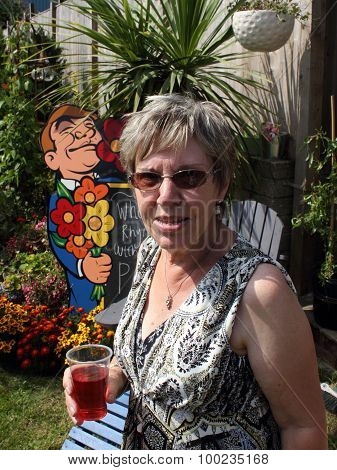 A mature lady having refreshment in a garden