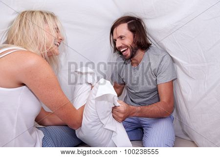 young fun couple pillow fighting under sheet in home bedroom