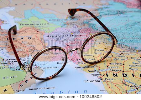 Glasses on a map of Asia - Muscat