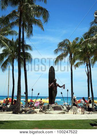 Female Tourist Look At Duke Kahanamoku Statue Holding Leis At Waikiki Beach