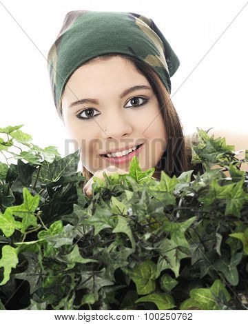 Close-up of a beautiful teen girl in a camouflage head scarf peeking over thick, green ivy.  On a white background.