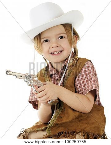 Closeup of a preschool cowgirl happily holding her gun.  On a white background.