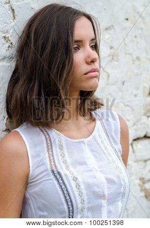 Portrait of the beautiful sad girl in white dress