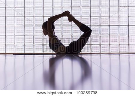 Young woman practicing in a yoga studio. This pose is called bow pose or dhanurasana.