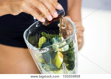 Hands of a woman adding maple syrup and spirulina to a green detox juice.