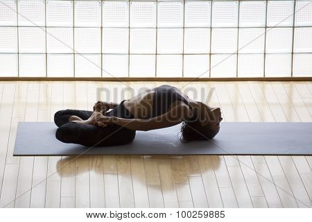 Above shot of a young woman practicing in a yoga studio. Fish pose, or Matsyasana with lotus legs.