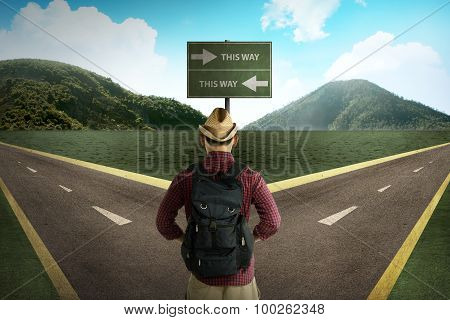 Asian Tourist Standing In The Middle Of Crossroad