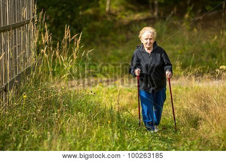 Mature woman engaged in Nordic walking outside the city.