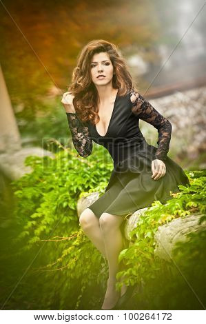 Charming young brunette woman in black dress sitting on wall covered with green leaves