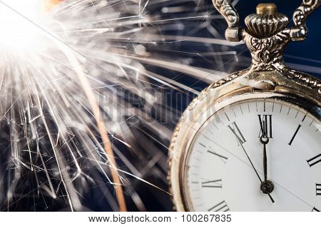 Holiday Background With A Sparkler And New Year Clock