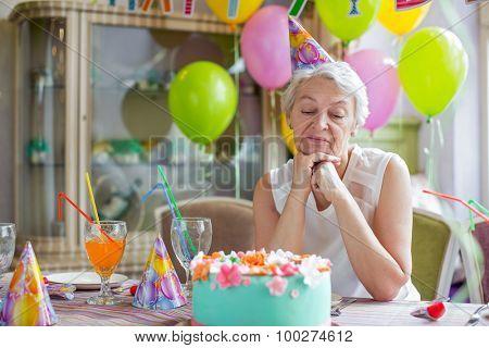Sad elderly woman at a birthday party