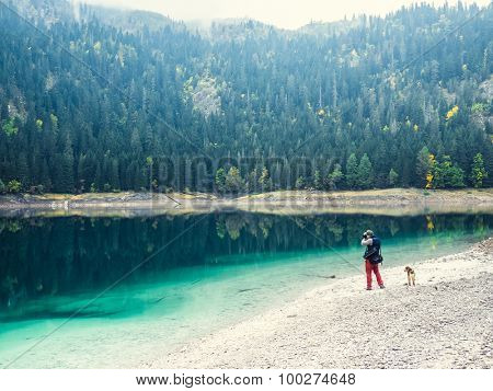 Young man with dog walks near the lake