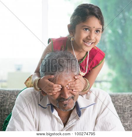 Happy Indian family at home. Asian girl surprising her father by covering dad eyes. Parent and child indoor lifestyle.