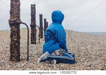 Young Woman Sitting By A Rusty Fencew On The Beach