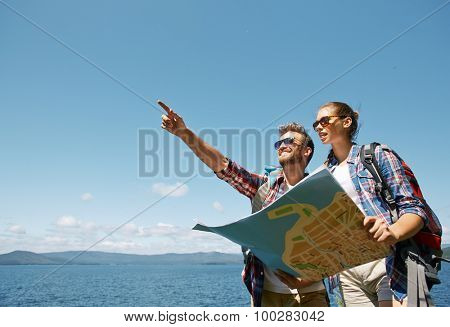 Young couple with map choosing route for further trip