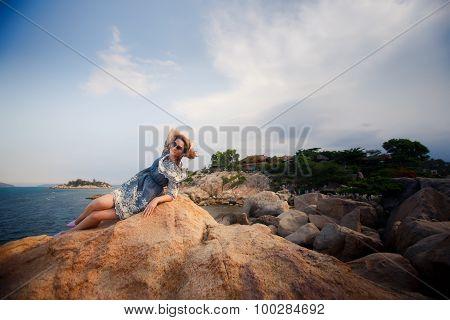 Girl In Short Grey Frock Lies On Rock Against Stones Plants