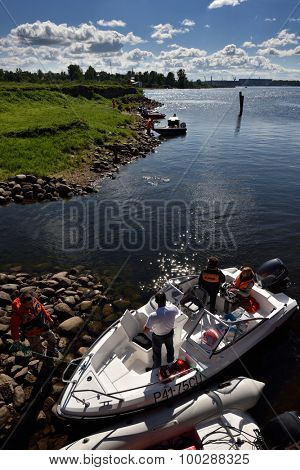 ORESHEK FORTRESS, LENINGRAD OBLAST, RUSSIA - AUGUST 15, 2015: Athletes resting between stages of the River marathon Oreshek Fortress race. This international motorboat competitions is held since 2003