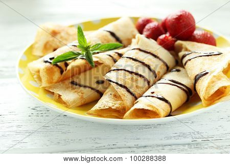 Tasty Rolled Pancakes With Strawberry On White Wooden Background