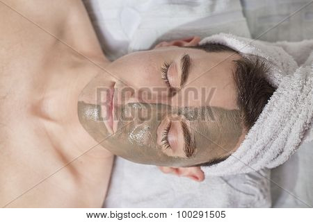 Relaxing Man With A Mud Mask On This Face