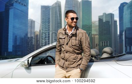 travel, tourism, road trip, transport and people concept - happy man near cabriolet car over city skyscrapers background