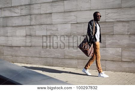 Fashion Stylish Young African Man In Sunglasses And Black Rock Leather Jacket With Bag Walking Over