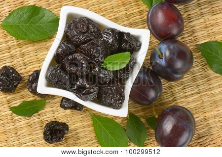 fresh and dried plums on bamboo place mat