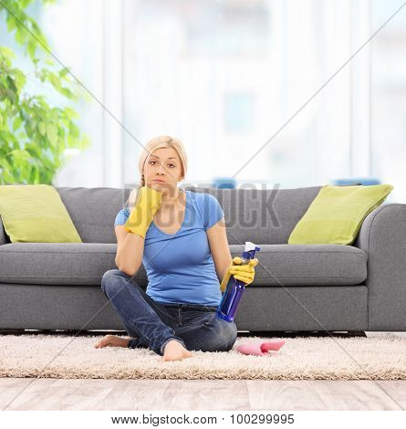 Female cleaner with yellow cleaning gloves holding a spray bottle and sitting in front of a gray sofa at home shot with tilt and shift lens