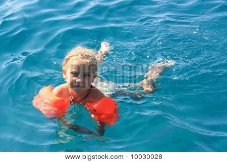 Girl's Swimming In The Sea In Armlets