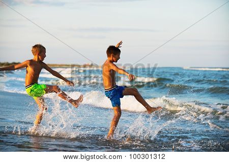 Two boys adolescence playing in the sea water splashing feet water