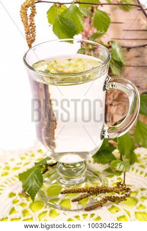 Isolated transparent cup of birch juice on the background of birch trunk