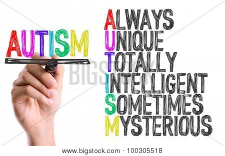 Hand with marker writing the word Autism