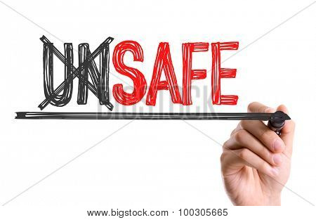 Hand with marker writing the word Unsafe Safe