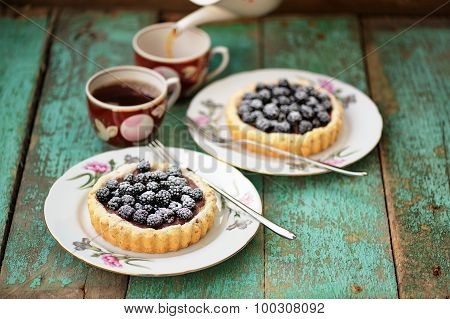 Tasty Cakes With Fresh Wild Blackberries And Icing Sugar With Two Cups Of Black Tea