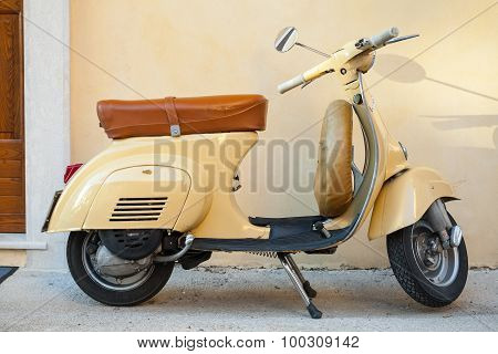 Classic Yellow Vespa Scooter Near The Wall