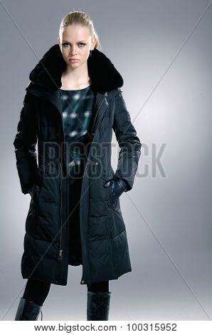 fashion model in black coat clothes posing in studio