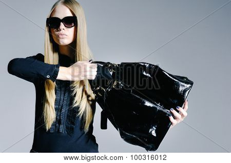 portrait of fashion model in modern clothes holding handbag â??gray background