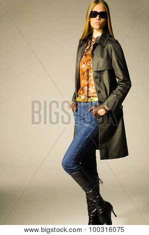 Full length fashion girl in  coat posing on light background