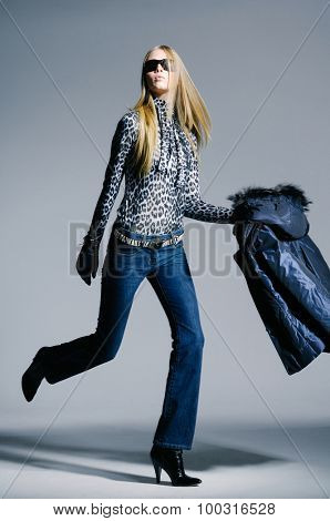 Full body fashion model in fashion dress walking in light background