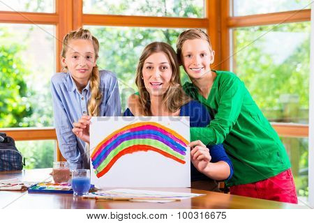 Mother with kids painting pictures with water color