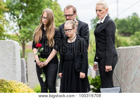 Family on cemetery or graveyard mourning deceased relative