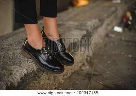 Closeup Of Young Woman Legs Wearing Black Shoes